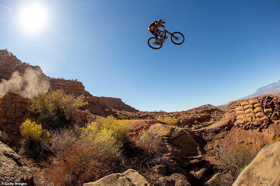 Freestyle Mountain bike rider flies across a ravine Red