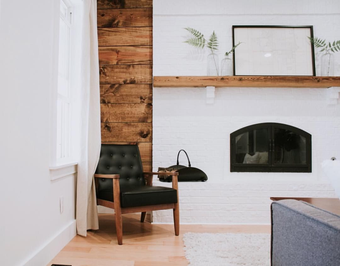 Massive White Brick Fireplace With A Shiplap Wall Behind It A Black Leather Chair Compliments The Space White Brick Fireplace Fireplace Design Brick And Wood