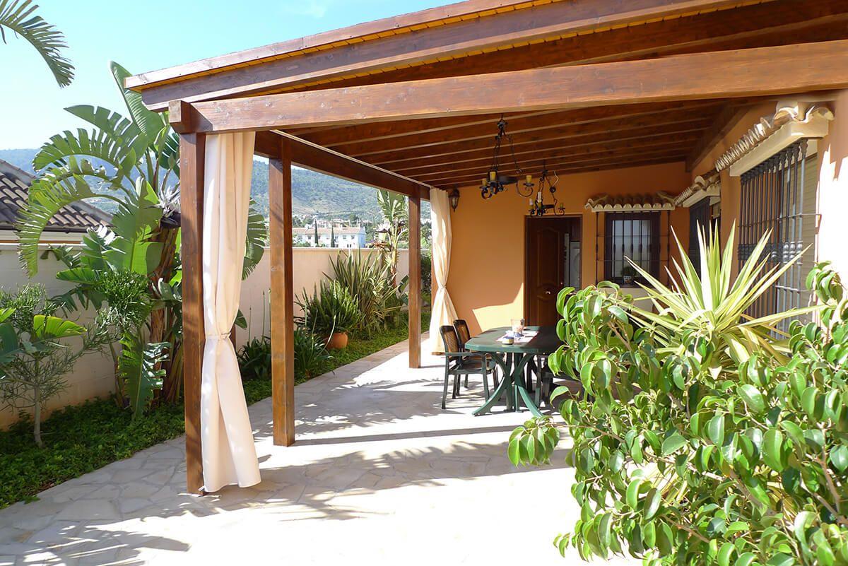 Coberti porche de madera de estilo cl sico con cortinas porche madera clasico jardin Porche jardin madera