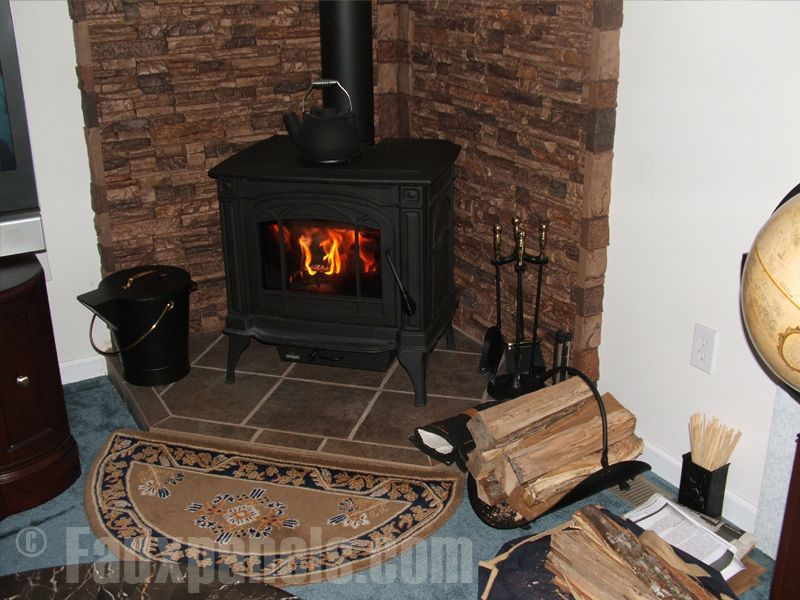 A corner wood burning stove accented with faux stacked stone