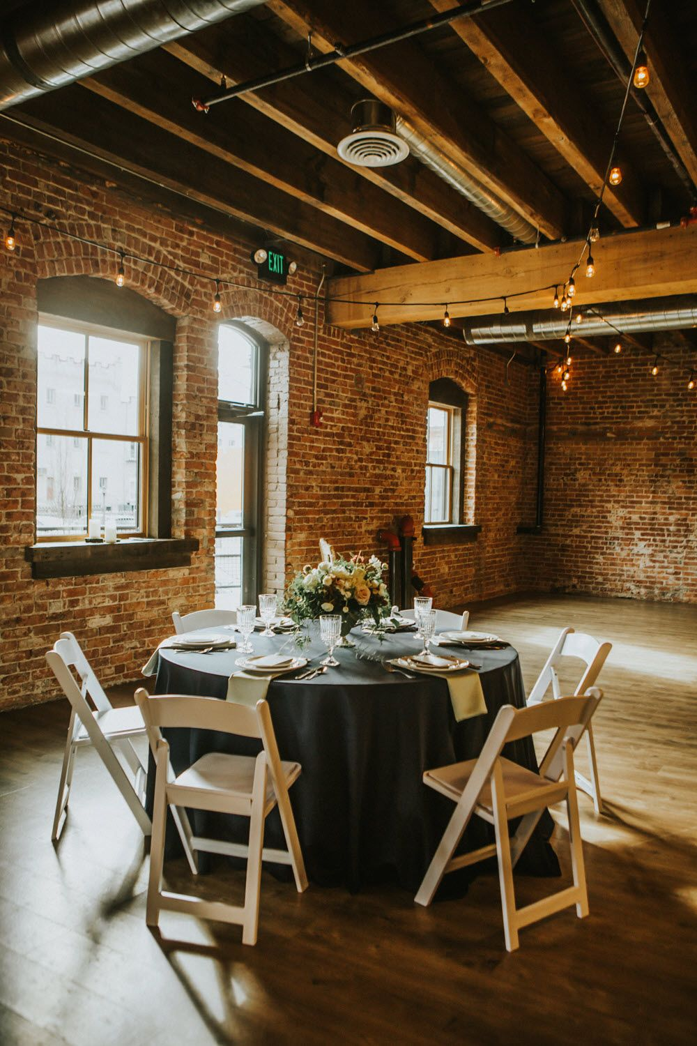 Indoor wedding decorations done right when you mix brick interiors with hanging lights black tablecloths and short centerpieces also rh pinterest