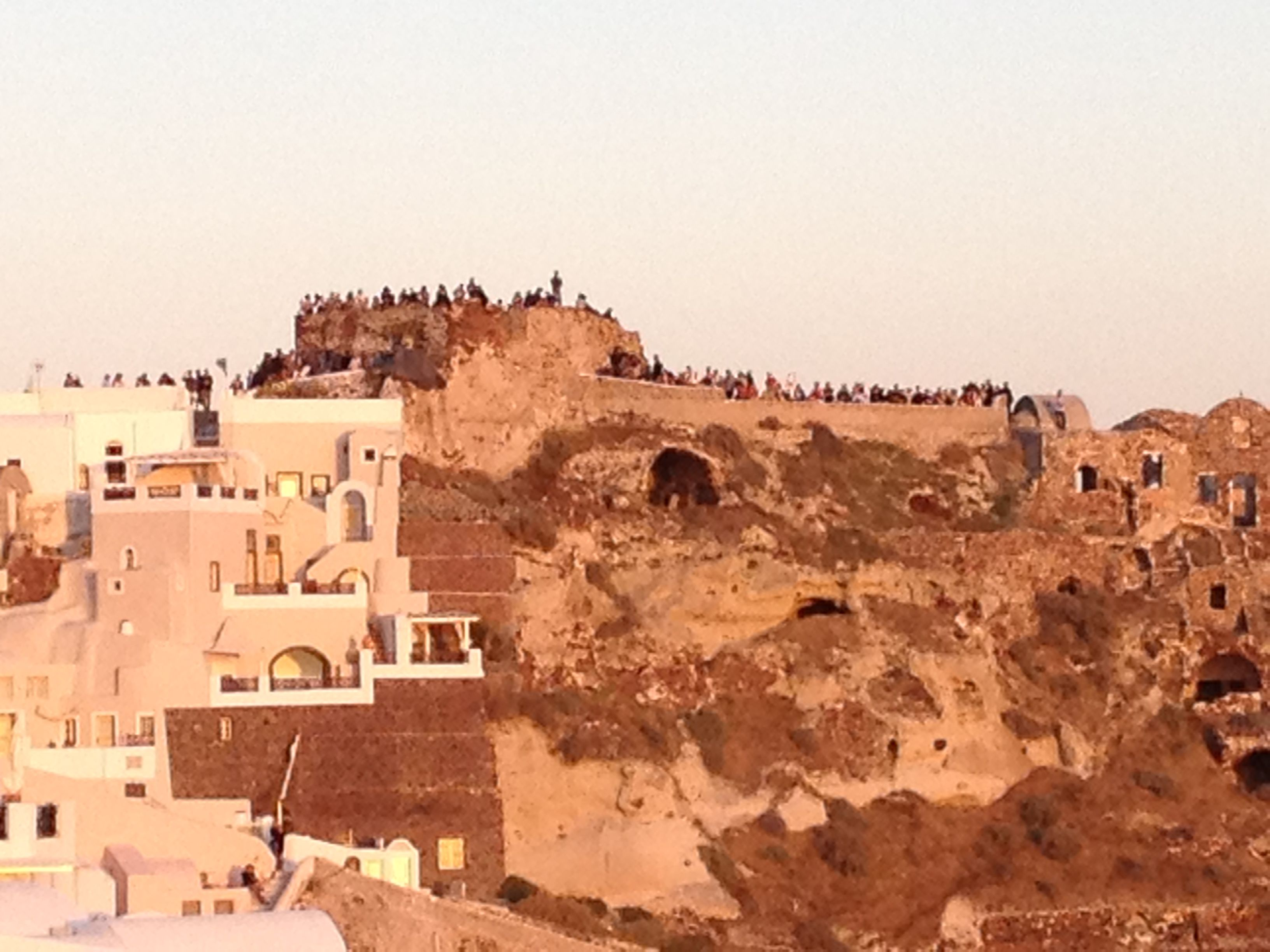 View of Oia castle from our house with people watching the sunset
