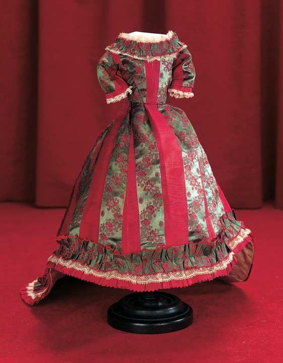 """Silk Poupee Gown with Elongated Train - To fit about 15"""" poupee. Of a fine red silk fabric with interwoven silk ribbon bands,having fitted bodice with set-in waist,3/4 sleeves,rounded neckline with gathered ruching with scalloping at the neckline that is repeated at the hem,extending around the back to the train,with lace edging at neckline,cuffs and hem. French - circa 1870."""