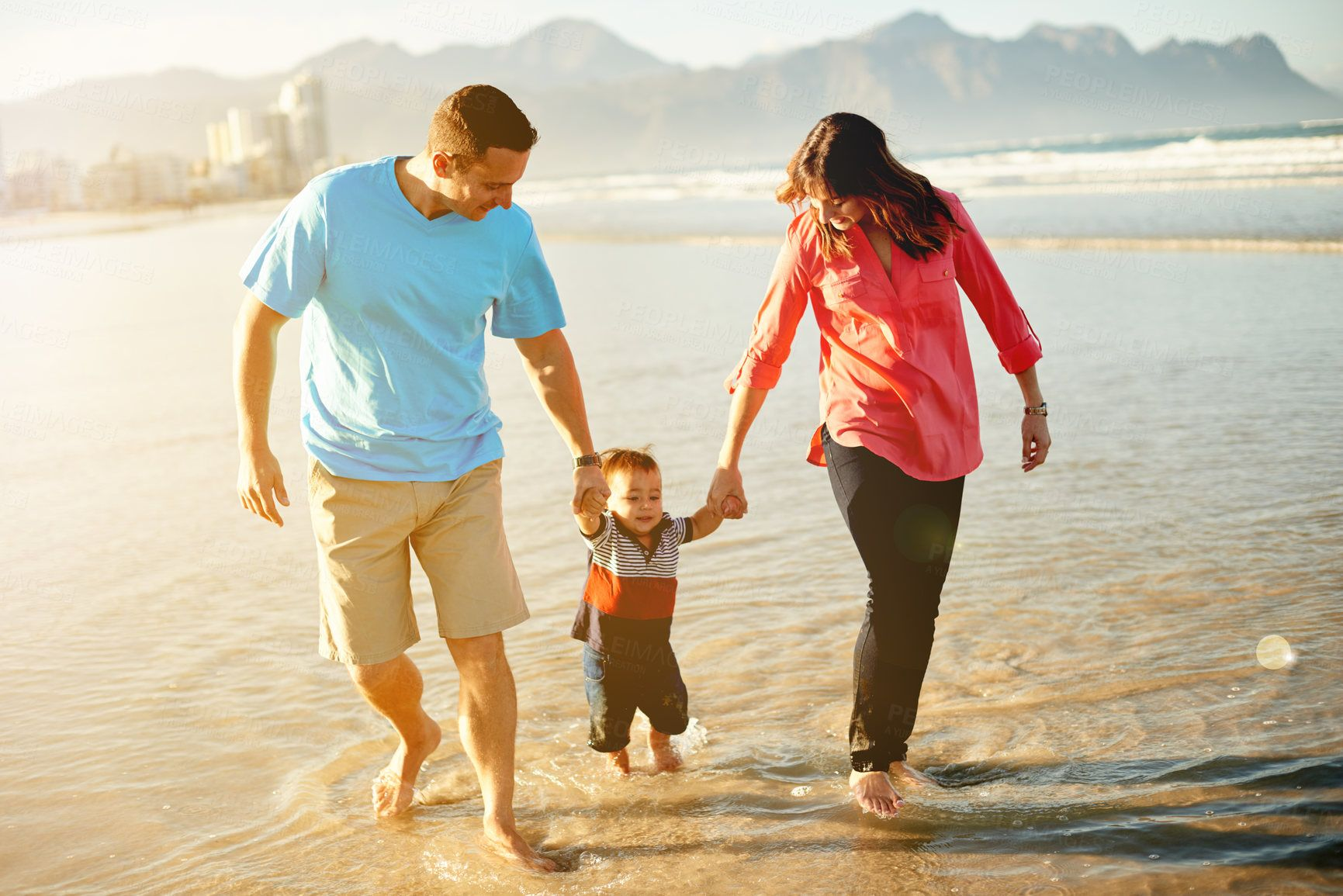 Shot of a family of three enjoying a day at the beach - stock photo #1358039