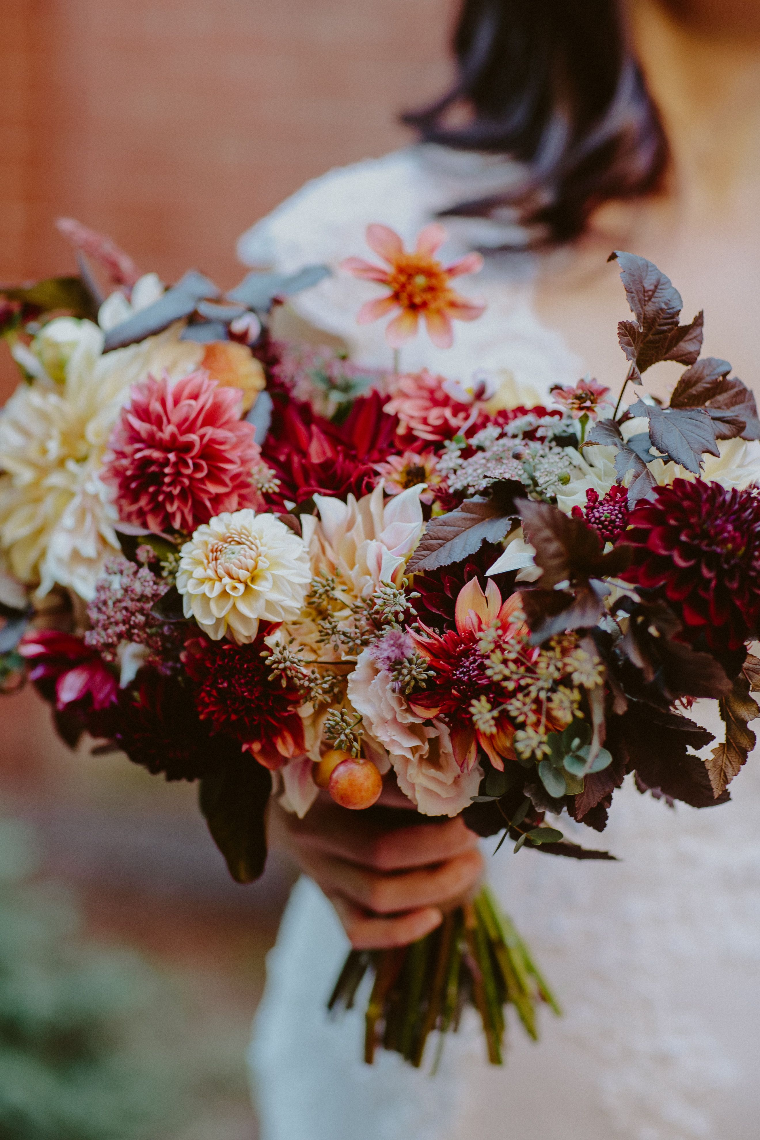 Autumn bridal bouquet in garnet, peach, and burgundy hues. Dahlias and herbs. Grown and designed by Love 'n Fresh Flowers. Photo by Storytellers & Co.