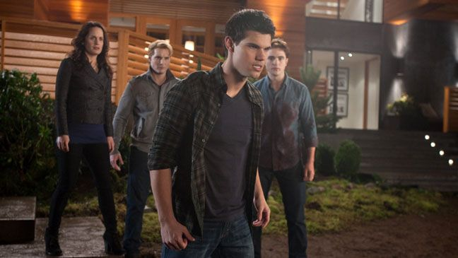 The Cullens stand behind an enraged Jacob, while Edward (Robert Pattinson) dons a blood soaked shirt.