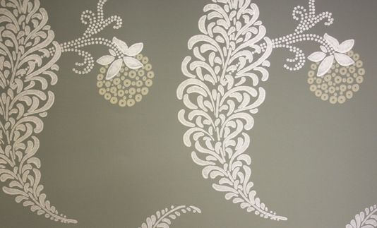 Rosslyn Wallpaper A delicate floral design wallpaper in metallic silver with rich cream flower, on a khaki green background.