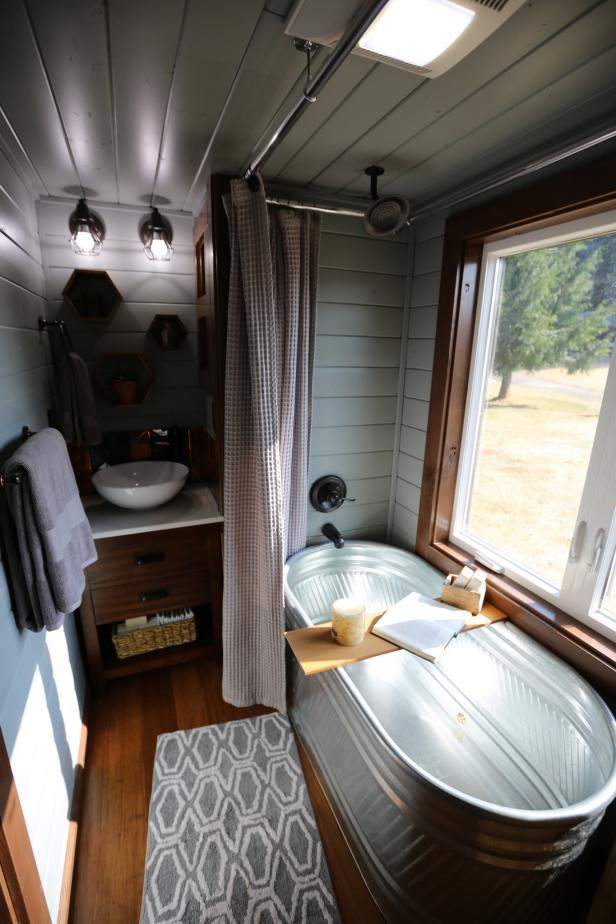 Luxurious tiny bathroom features a full sized galvanized soaking tub a relaxing station