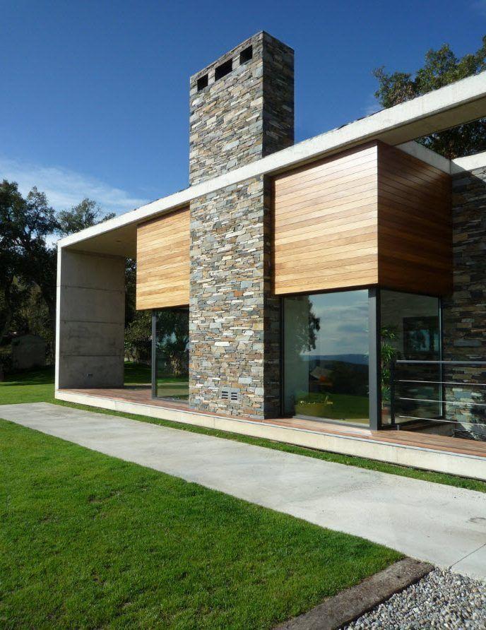 Dise o de moderna casa construida en terreno rectangular fachada combina hormig n piedra y - Casas prefabricadas madera y piedra ...