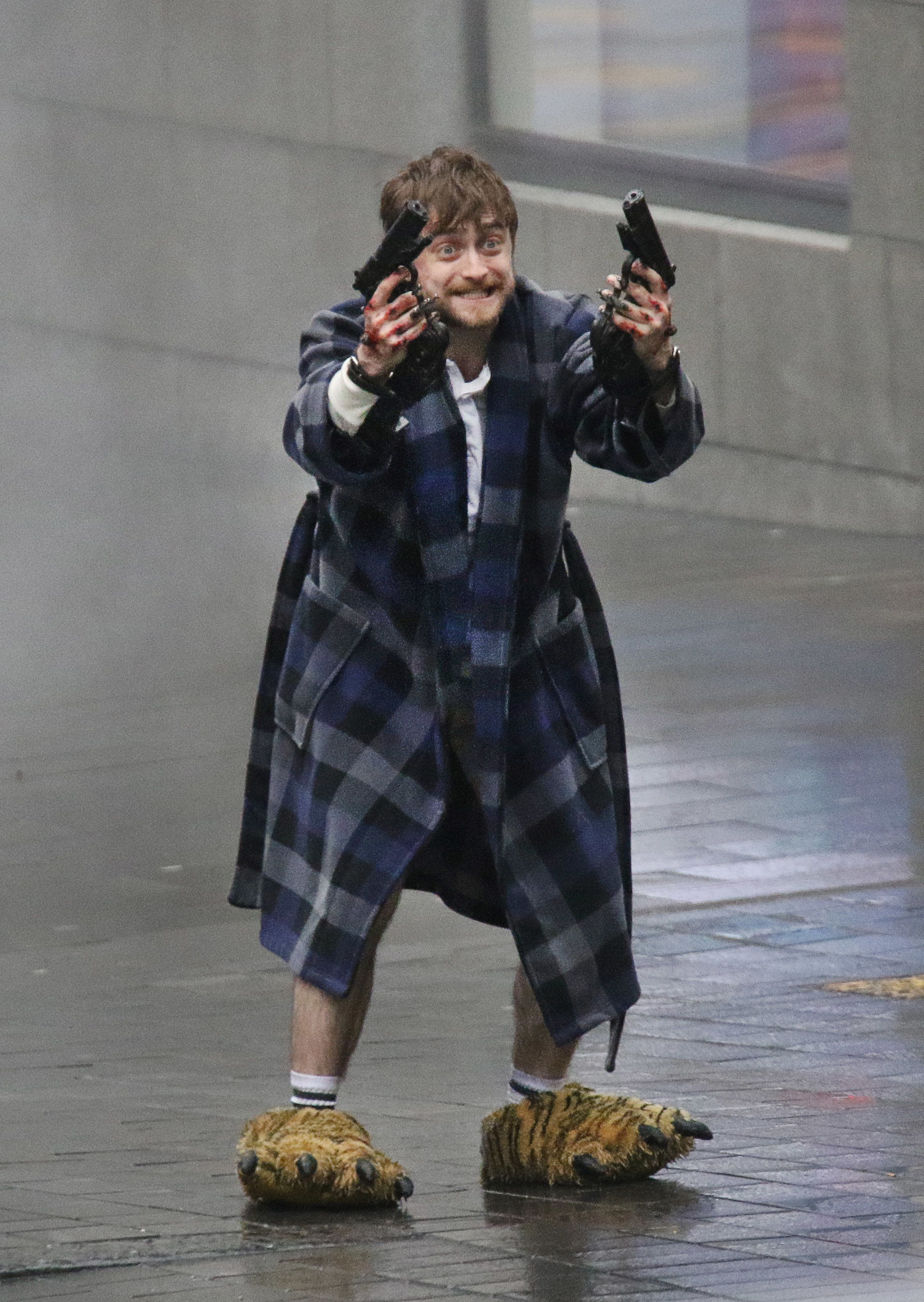 Photo Of Daniel Radcliffe Holding Guns In Crazy Slippers Becomes A Magical Meme Daniel Radcliffe Harry Potter Funny Daniel Radcliffe Harry Potter
