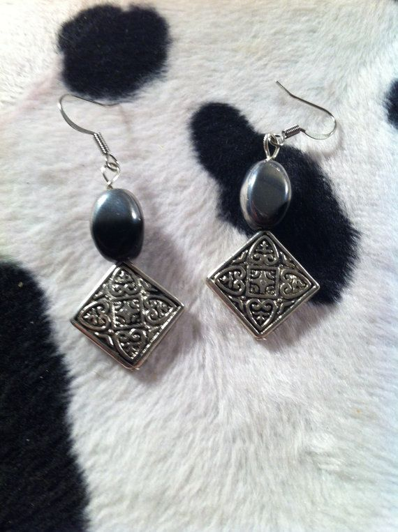 Uniquely designed hand-beaded earrings are made of black / silver helix glass…