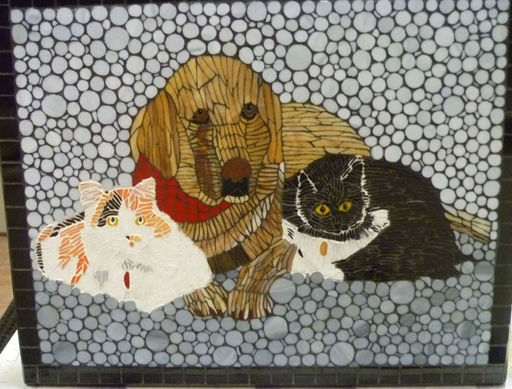 """Amber, Jasper and Holly    Amber, Jasper and Holly were long-time beloved mascots of the Souris Valley Animal Shelter.     This reclaimed mosaic table measures 22""""w x 18""""d x 18.25""""h. Each piece of glass was cut, shaped and the edges were ground to make them fit.  I used several different colors of grout to provide shading. The glass is made by Spectrum and the mosaic was grouted and then sealed with Diamond Crete sealer. This table took over 75 hours to complete."""