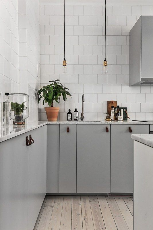 Grey kitchen cabinets with leather pulls, exposed lighting and white tiles  Home ...