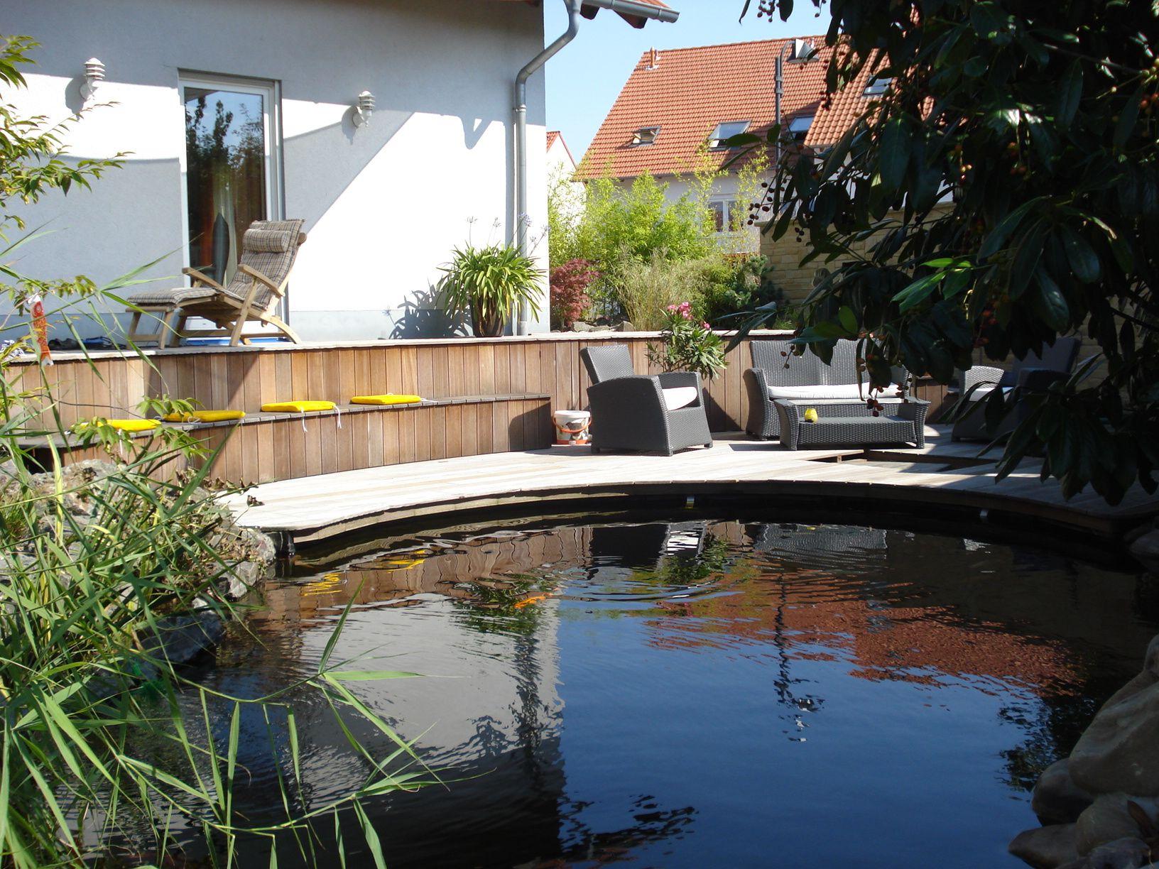 Idyllischer Wohngarten mit Koi Teich umrandet von Holzdeck zum Entspannen im Schatten