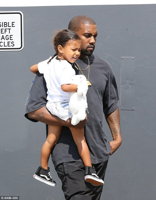 e4d69522bf5b9 Kanye West protectively carries slumbering daughter North in his ...
