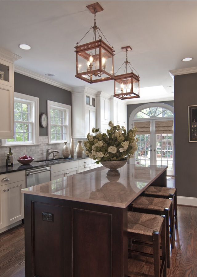 I'm impressed with the size and shape of this kitchen. I like the gray walls and white trim. Also the island top.