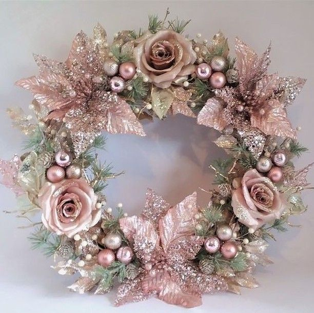 Photo of Beautiful pink glossy wreath made of poinsettias, roses, sprays, pearls and pins …