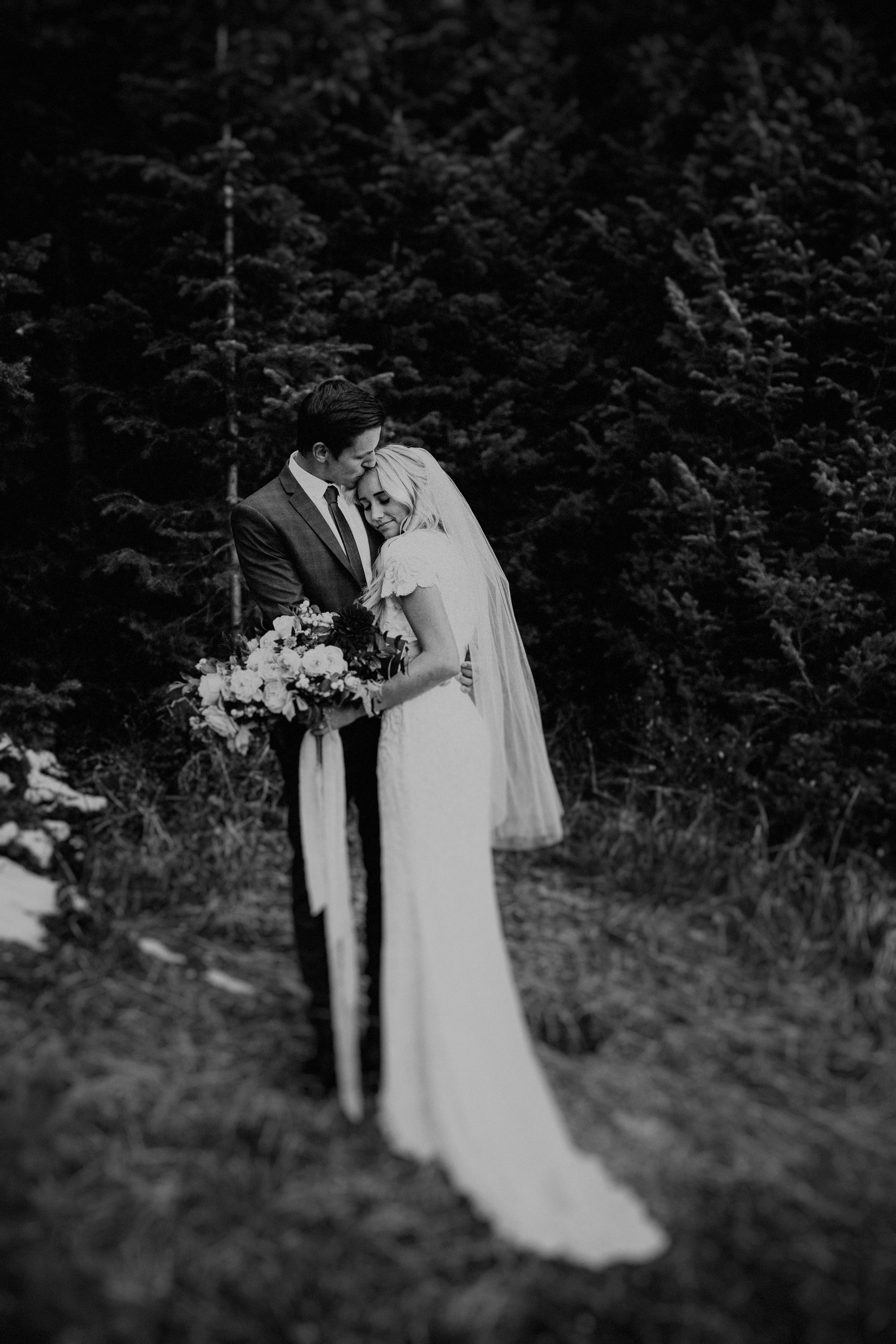 Far away shot of bride and groom in black and white in the forrest