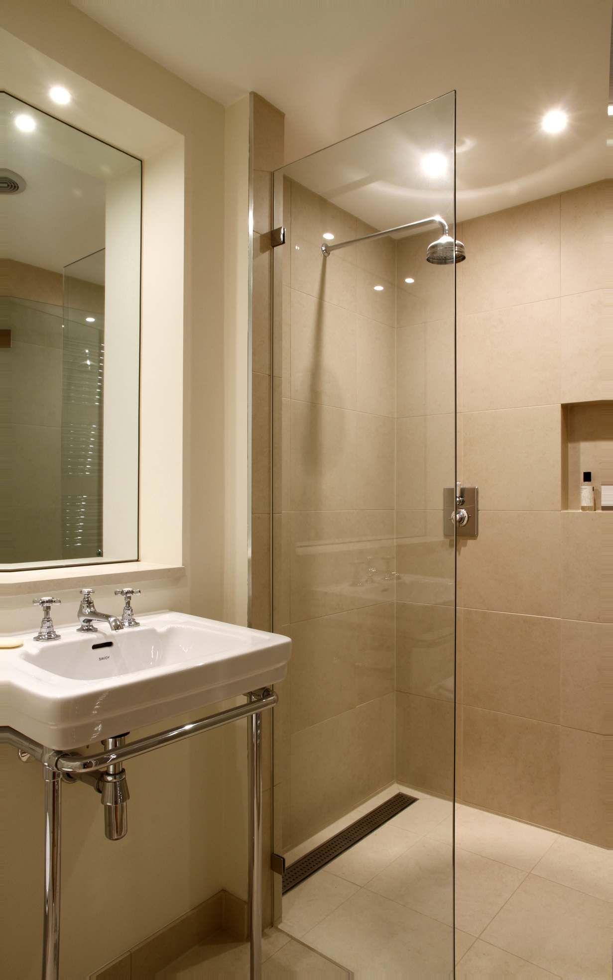 Basement bathroom glass wall and long drain. Feels airy