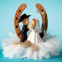 Get ready for a romantic touch of the frontier! This Western Couple Horseshoe Cake Topper is one of our favorite cowboy cake decorations. It features a cute bride and groom in fun western finery as they lean in for a kiss. Each Horseshoe Wedding Cake Topper is framed by a wooden horseshoe that's accented by a pair of dangling silver cowboy boots. Small wooden hearts tied to a tiny lasso rest at the couple's feet. The base of the cake topper is covered in a bed of ruffled white lace…