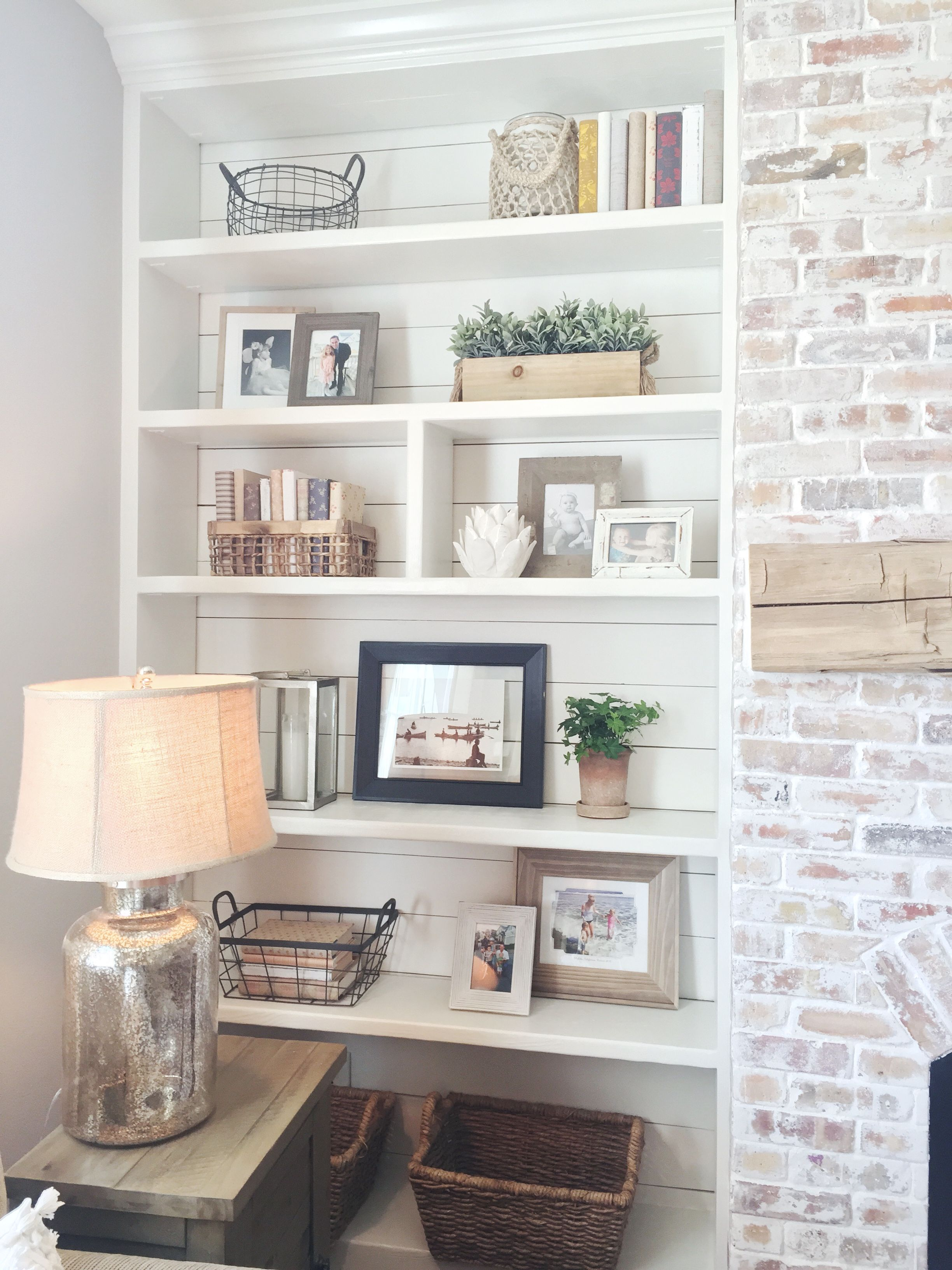 Builtin bookshelves styling shiplap whitewash brick fireplace