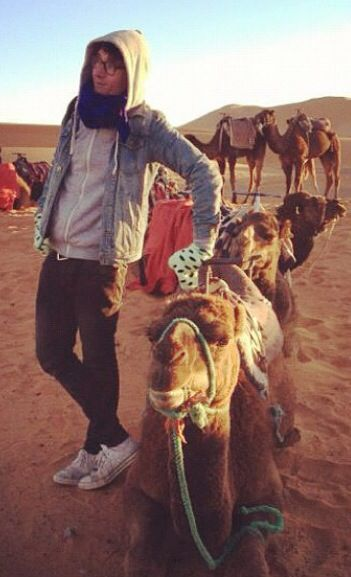 Dan Smith of Bastille, in a hoodie and scarf, with socks on his hands, with a camel