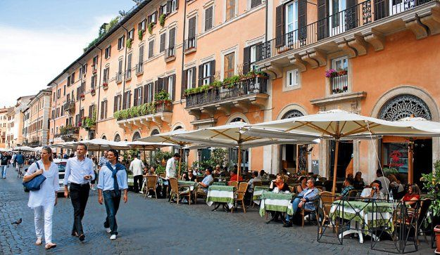 PARASOLES EN LA PLAZA. Un frente de la Piazza Navona, que está casi completamente bordeada por restaurantes pintorescos. En sus cartas no faltan los clásicos, como pizzas y pastas.
