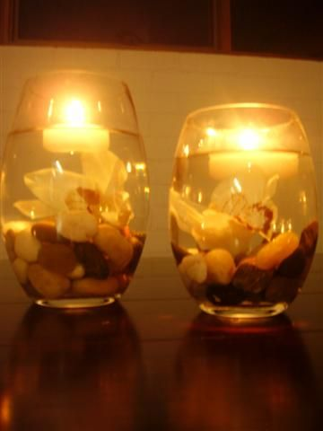 Centerpiece with lake stones and a flower in water, and a floating candle on top.