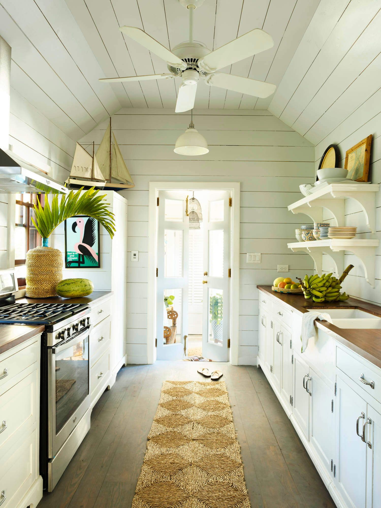 a galley like kitchen that leads to a shaded outdoor living space island harbour island on outdoor kitchen and living space id=55148