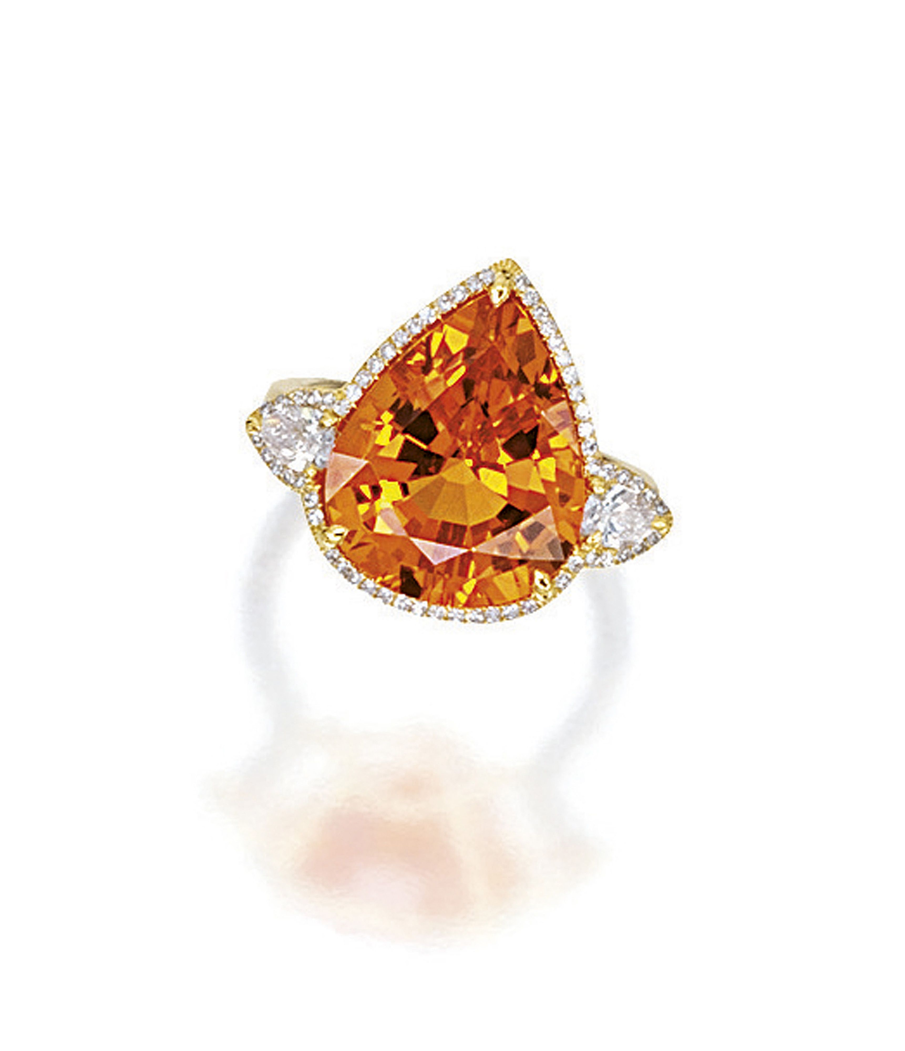 SPESSARTITE GARNET AND DIAMOND RING. Centring on a pear-shaped spessartite garnet weighing 10.26 carats, flanked on each side by a pear-shaped diamond, surrounded by brilliant-cut diamonds, mounted in platinum and 18 karat yellow gold. Sotheby's.