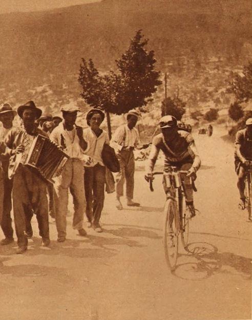 Tour de France 1927. 15^Tappa, 6 luglio. Tolone > Nizza. Col de Braus. Un suonatore di fisarmonica italiano per Maurice De Waele (1896-1952) e, alle sue spalle Julien Moineau (1903-1980) [Le Miroir des Sports]