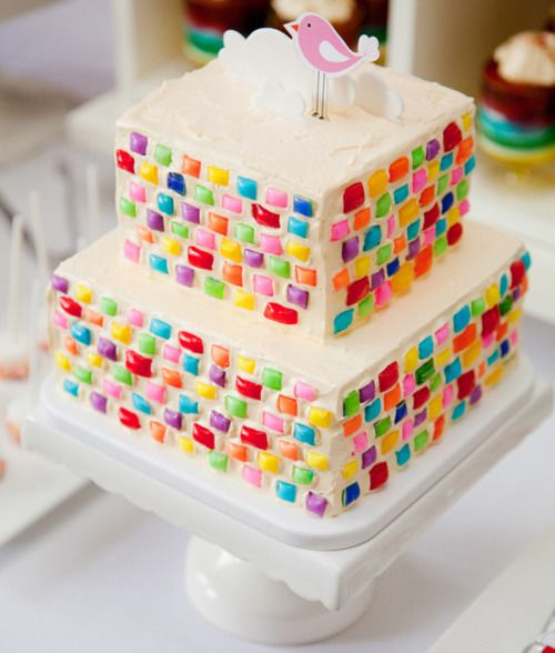 Colorful ribbon candy bits around two tier white cake squares I