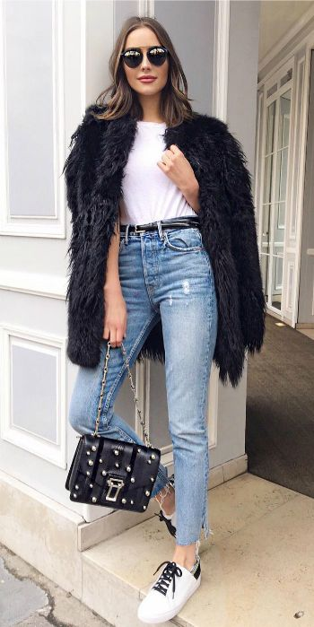b152fb41018 Olivia Culpo + black faux fur coat + high waisted denim jeans + retro white  + black sneakers + chic spring style + studded leather handbag + classic  shades.