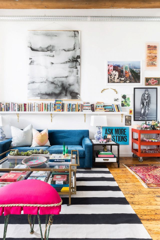 Eclectic living room with high ceilings, large art, floating bookshelves and a blue velvet sofa