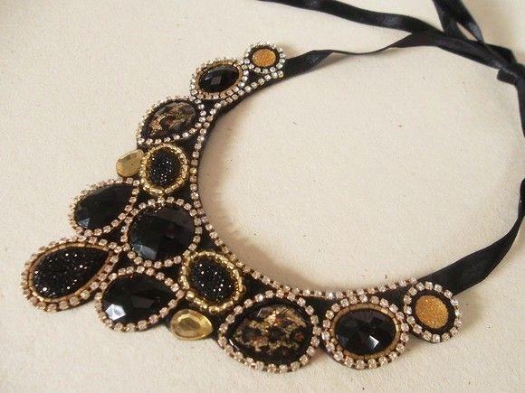 Maxi colar preto com strass e detalhes em dourado. Com chatons acrílicos e de resina, e pedrarias bordadas à mão. Peça única; R$90,00