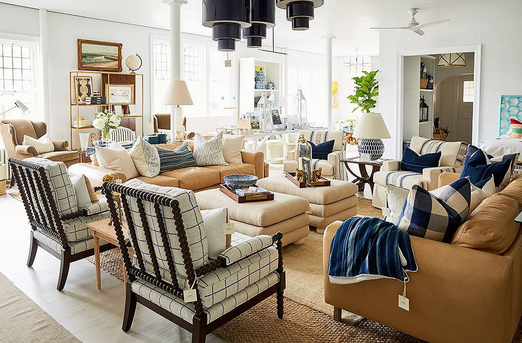 A Living Area In Neutral Hues Features Spindle Chairs By Miles Talbott,  Vintage Accents, And Cylindrical Pendants Inspired By The Swinging U002760s.