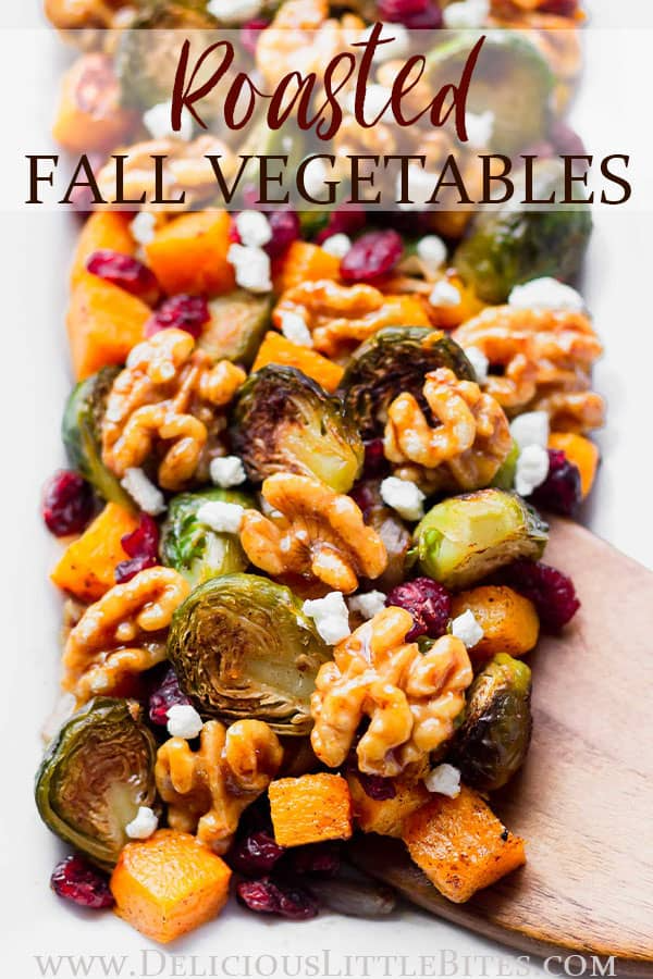 This easy-to-make Roasted Fall Vegetables recipe is a delicious blend of savory butternut squash, Brussels sprouts and shallot with bursts of cranberry sweetness in every bite. Maple walnuts add texture and crunch, while optional creamy goat cheese brings a hint of tanginess. It's perfect as a side dish to any fall dinner and especially at Thanksgiving. | #fallvegetables #sidedish #vegetarian #thanksgiving #thanksgivingsidedish