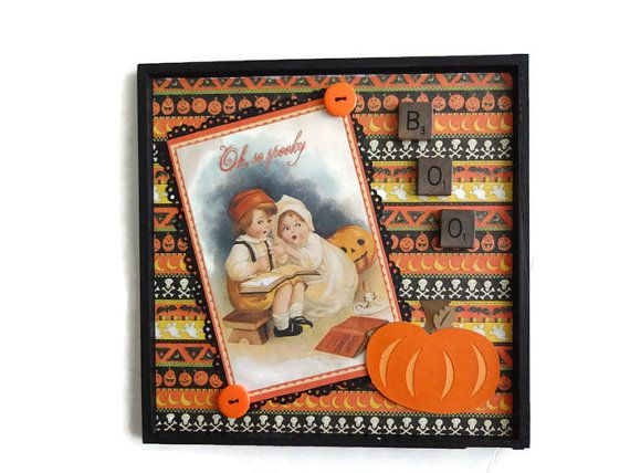 A vintage looking image graces the center of this Halloween wall decor. I added a colorful Halloween background and embellished the frame with a vintage looking image of a boy and girl reading ghost stories. I added a die cut layered pumpkin and some tiles distressed with black ink. A great Halloween decoration ready to hang. The wood frame is painted with black acrylic paint. Makes a great Halloween gift too. Measures 8 x 8 inches picture hook on back for hanging buttons,tiles and more…