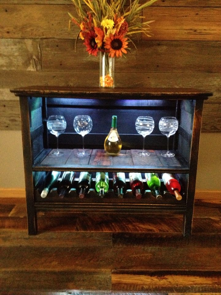 DIY wine rack made from old antique dresser.  complete with LED back lighting and barn board inlaid shelving.  it is painted black and distressed.  the top and shelves are stained in a darker color