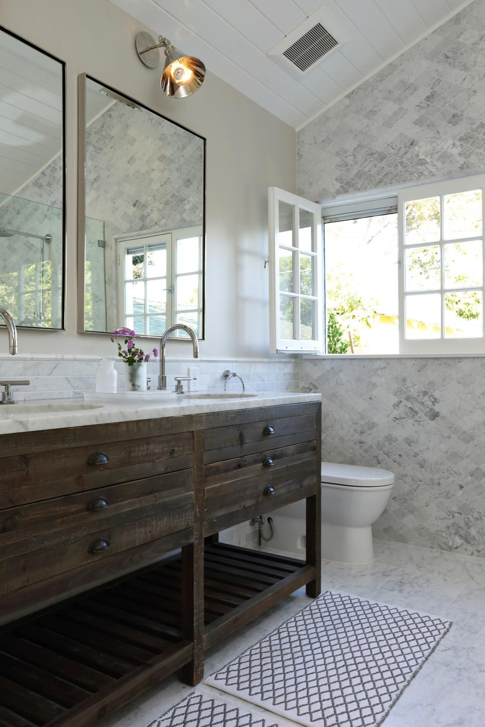 the rustic wood vanity is a striking contrast to the extravagant carrara marble floor and wall
