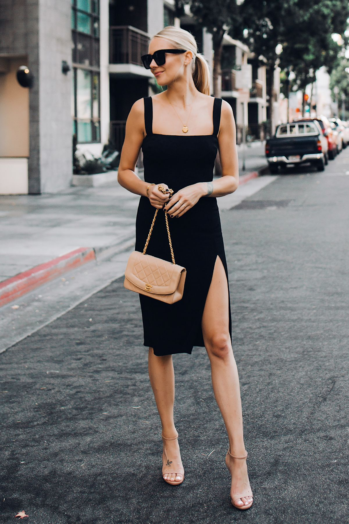Blonde Woman Wearing Reformation Black Dress Tan Ankle Strap Heeled Sandals Chanel Tan Diana Handbag Gold Coin Neck Dress And Heels Fashion Black Dress Outfits [ 1800 x 1200 Pixel ]