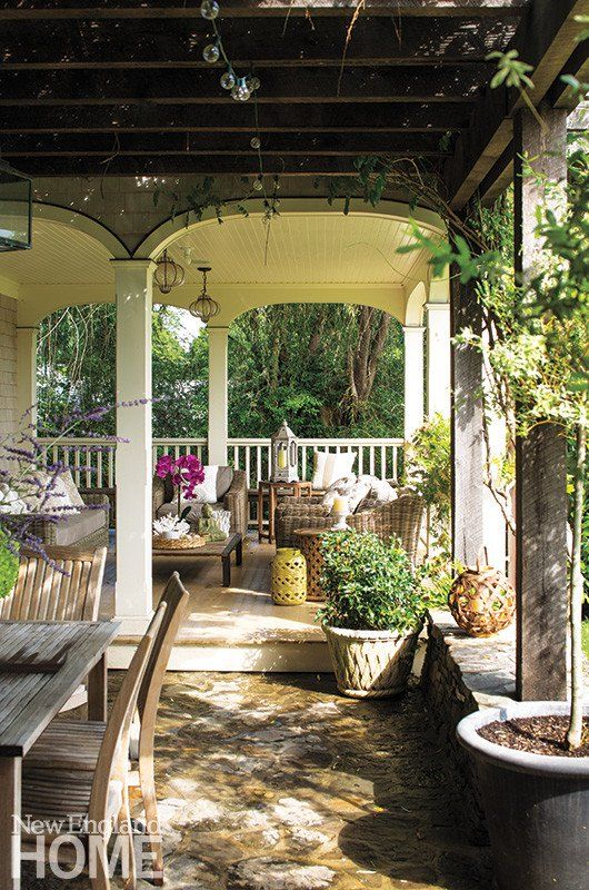An Outdoor dining table is set beneath a pergola dense with wisteria. The fieldstones for the terrace were carefully chosen to give the outdoor spaces an antique look.