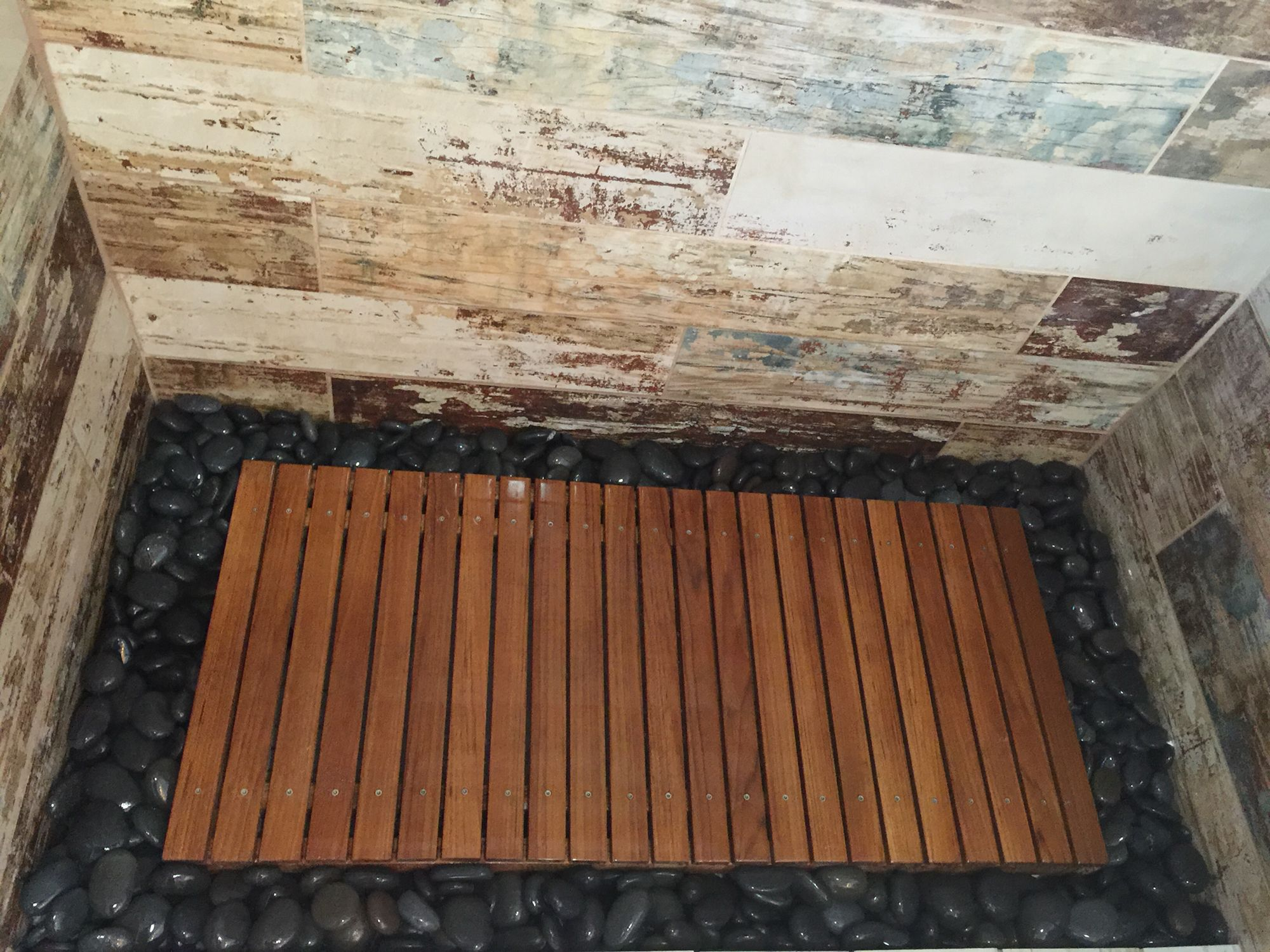 Teak wood shower floor surrounded by river rock walls tiles in ceramic bar wood tile designed by krysten petersen of wtbh llc st pete florida