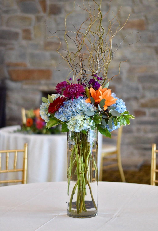 Colorful tall centerpiece featuring blue hydrangea, orange lilies, red  gerbera dais… | Blue wedding centerpieces, Blue hydrangea centerpieces, Wedding  table flowers
