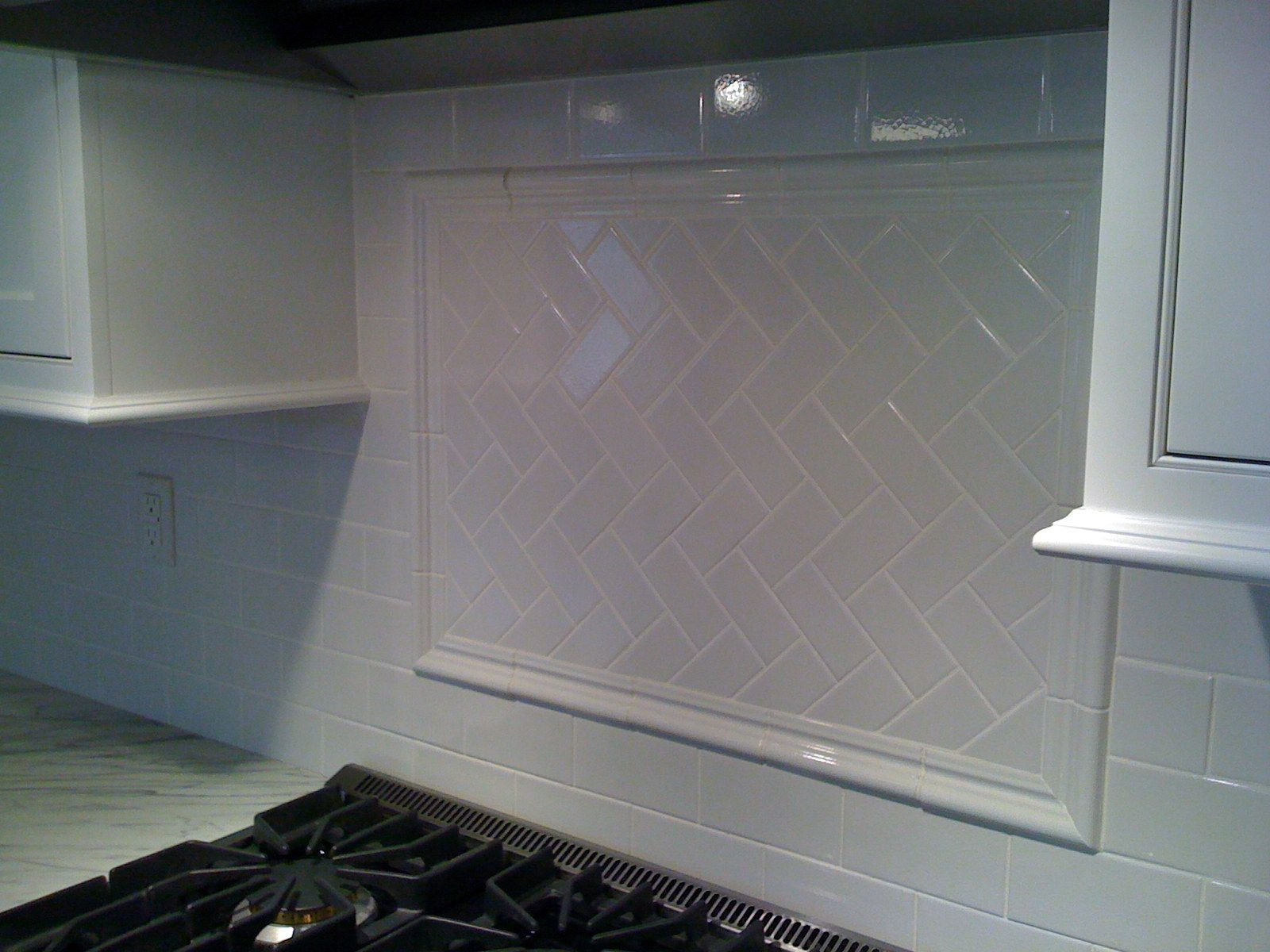 white subway tile with herringbone backsplash behind stove