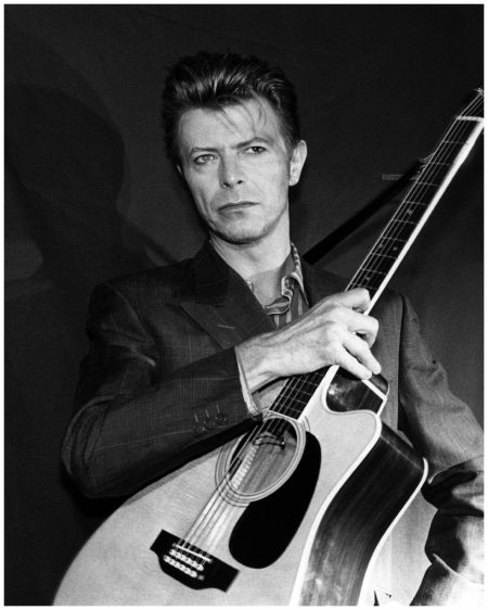 David Bowie performing on stage, with acoustic guitar, Sound Vision Tour, 1990. (Photo by Donna Santisi/Redferns)