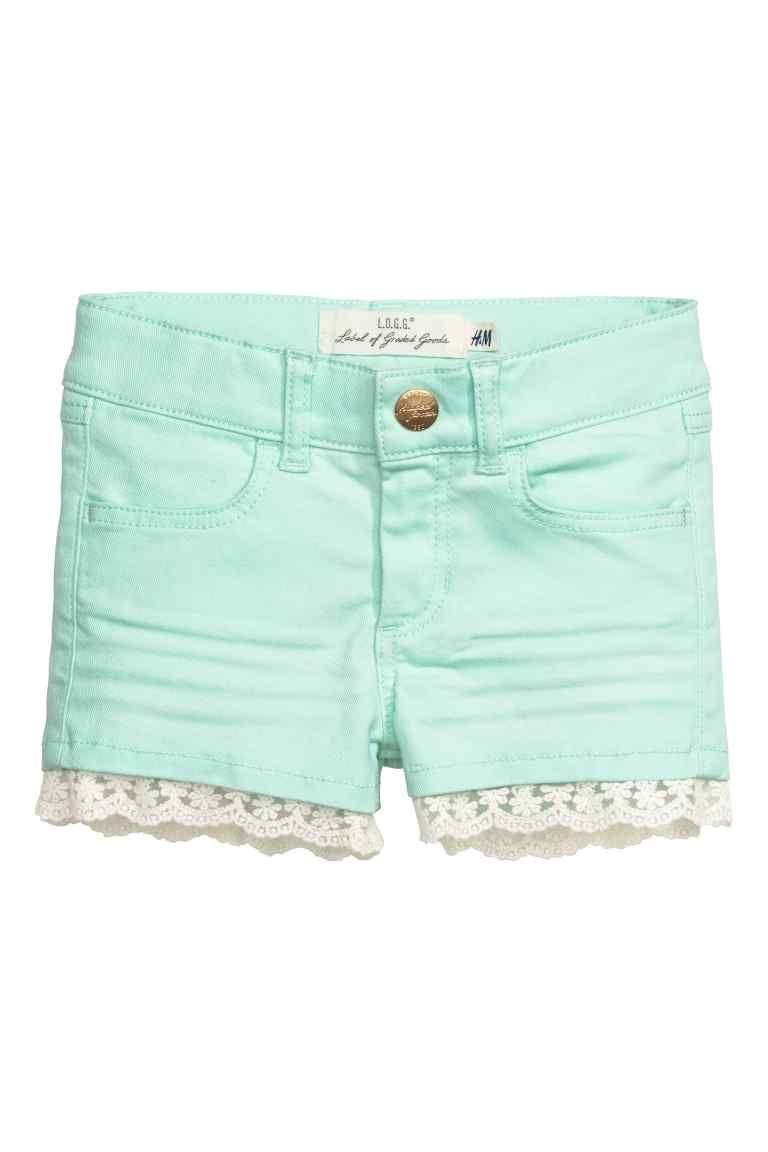 Pantalón corto de sarga: Pantalón corto en sarga de algodón elástica y lavada con cinturilla elástica ajustable, y cierre con cremallera y botón de presión. Bolsillos delanteros y traseros, y ribetes de encaje en los bajos.