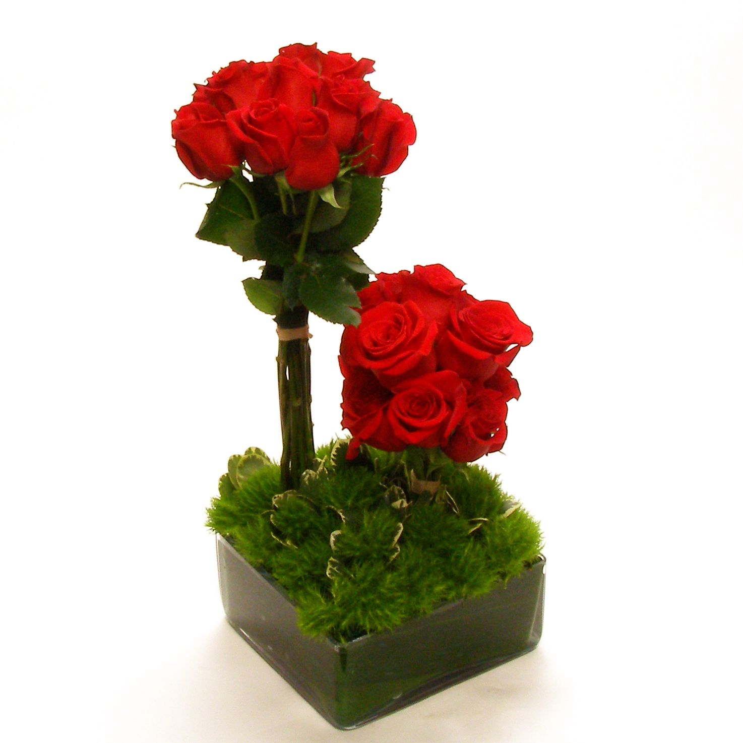 A modern treelike floral arrangement of red roses is a