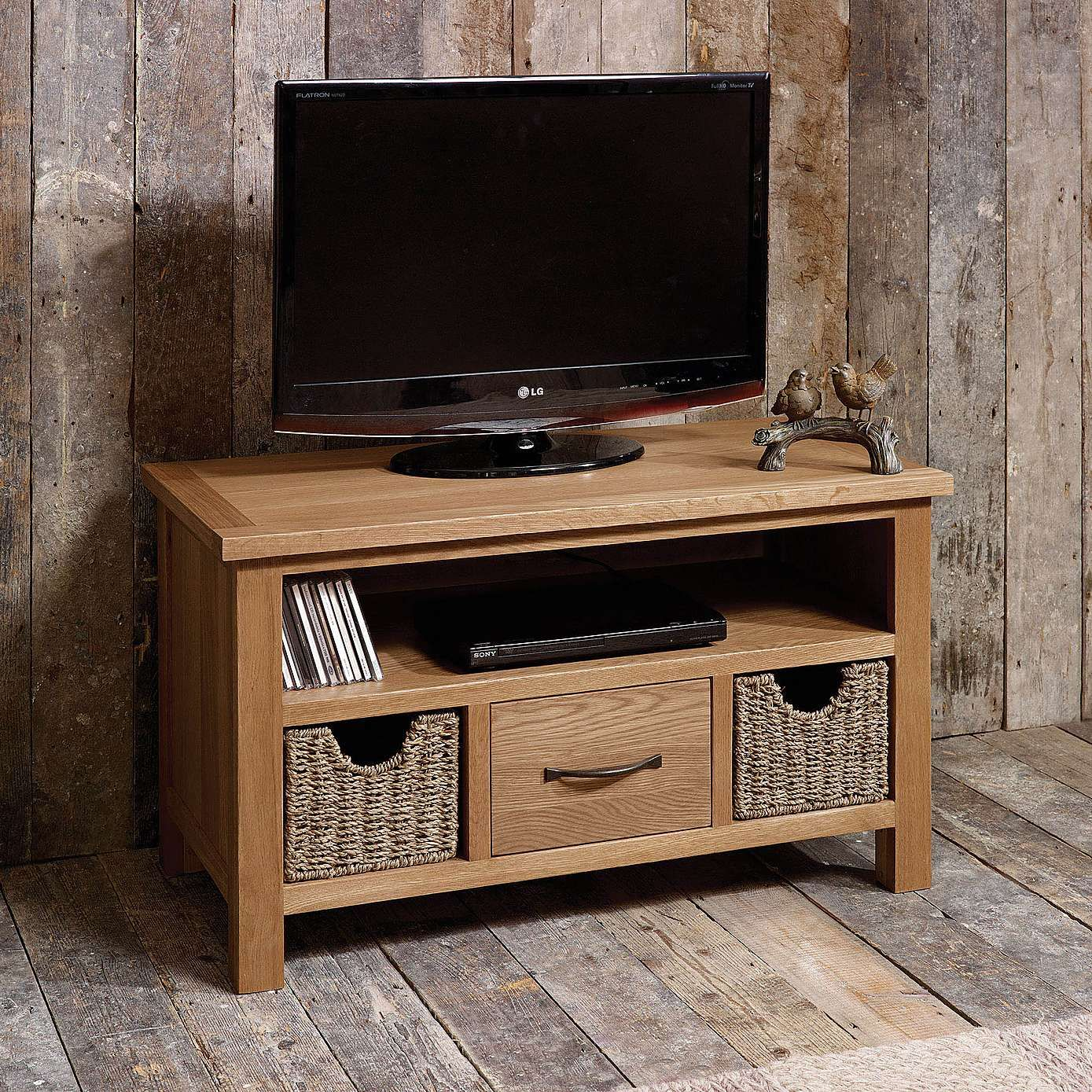 crafted with a light oak veneer this small fully assembled tv stand provides ample storage space including a shelf for electronic equipment