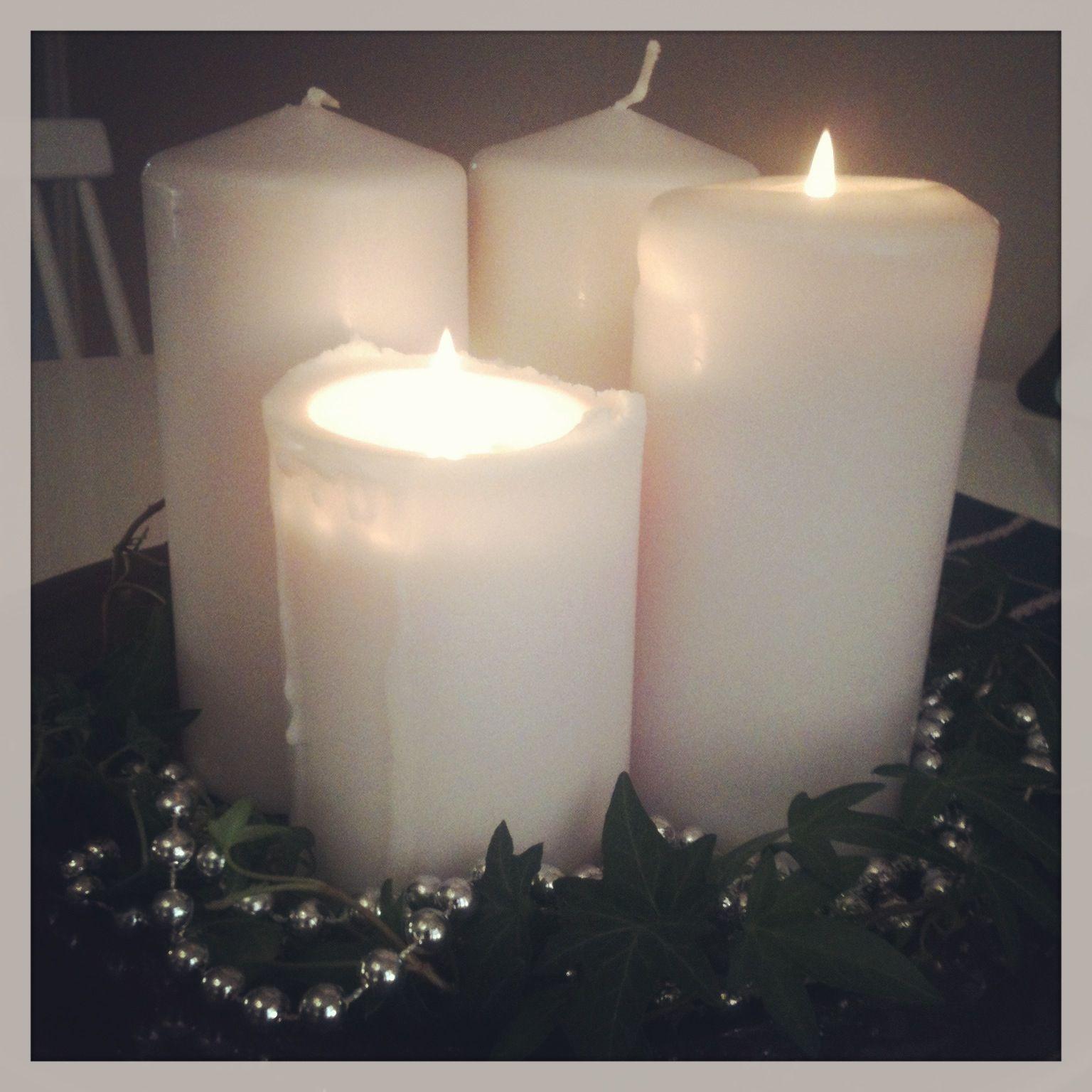"""Vår adventsljusstake: fyra vita blockljus, """"silver-pärlor"""" och murgröna på ett vinrött fat."""